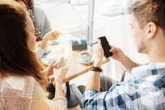 Amis attentifs à l'aide des téléphones portables Photographie stock