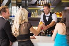 Amis attirants étant servis des cocktails Photos stock