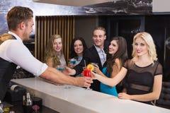 Amis attirants étant servis des cocktails Photos libres de droits