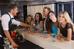 Amis attirants étant servis des cocktails Photographie stock
