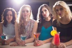 Amis attirants buvant des cocktails ensemble Photographie stock libre de droits