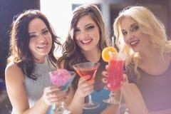Amis attirants buvant des cocktails ensemble Image stock