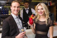 Amis attirants buvant des cocktails ensemble Images stock