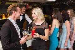 Amis attirants buvant des cocktails ensemble Photo stock