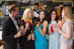 Amis attirants buvant des cocktails ensemble Images libres de droits