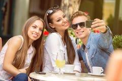 Amis au café prenant le selfie dans un café Photo stock