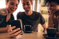 Amis au café utilisant le téléphone portable Image libre de droits