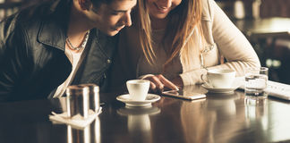 Amis au café utilisant un téléphone portable Photos stock