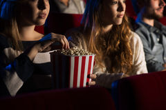 Amis au cinéma observant un film Photographie stock