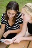 Amis au téléphone portable ensemble (belle jeune blonde et Brune image stock
