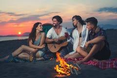 Amis autour du feu dans le coucher du soleil sur la plage Photographie stock libre de droits