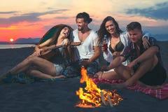 Amis autour du feu dans le coucher du soleil sur la plage Photos libres de droits