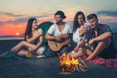 Amis autour du feu dans le coucher du soleil sur la plage Images libres de droits
