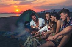 Amis autour du feu dans le coucher du soleil sur la plage Image libre de droits