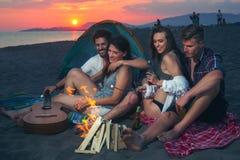 Amis autour du feu dans le coucher du soleil sur la plage Photographie stock
