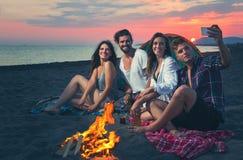 Amis autour du feu dans le coucher du soleil sur la plage Photo stock