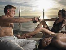 Amis avec Champagne On Deck By Sea au coucher du soleil Photographie stock libre de droits