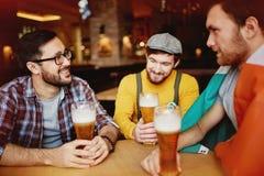 Amis avec de la bière au bar irlandais Photographie stock libre de droits