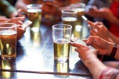 Amis avec de la bière et des smartphones à la barre ou au bar Photo libre de droits