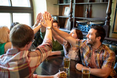 Amis avec de la bière faisant la haute cinq à la barre ou au bar Photos stock