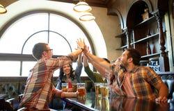 Amis avec de la bière faisant la haute cinq à la barre ou au bar Images stock