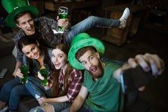 Amis avec de la bière faisant le selfie le jour du ` s de StPatrick Photo stock