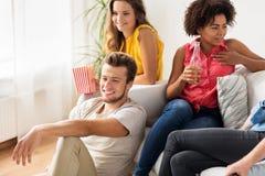 Amis avec de la bière parlant et regardant la TV à la maison Images stock