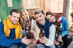 Amis avec de la bière passant le temps ensemble et regardant à l'appareil-photo Photos libres de droits