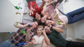 Amis avec des émotions heureuses jouant avec le mensonge de confettis ensemble et le sourire à la caméra pendant une partie à banque de vidéos