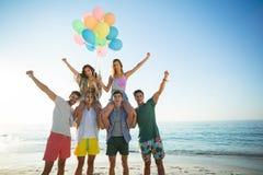 Amis avec des ballons d'hélium au beac Photo stock