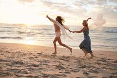 Amis avec des ballons sur la plage appréciant le jour d'été Photographie stock