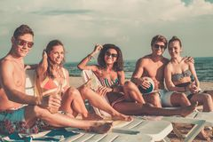 Amis avec des boissons détendant sur une plage Photographie stock libre de droits