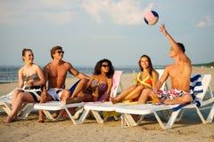 Amis avec des boissons détendant sur une plage Photo libre de droits