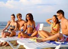 Amis avec des boissons détendant sur une plage Image stock