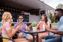 Amis avec des boissons se reposant à la table au camion de nourriture Images libres de droits