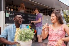 Amis avec des boissons se reposant à la table au camion de nourriture Image stock