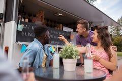 Amis avec des boissons se reposant à la table au camion de nourriture Photo libre de droits