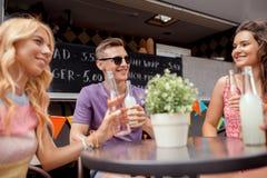 Amis avec des boissons se reposant à la table au camion de nourriture Photo stock