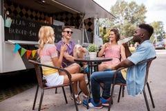 Amis avec des boissons se reposant à la table au camion de nourriture Photographie stock libre de droits