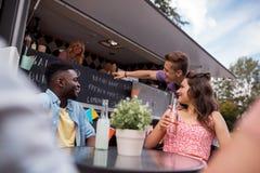 Amis avec des boissons se reposant à la table au camion de nourriture Photographie stock