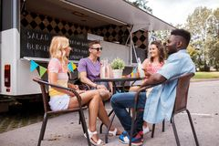 Amis avec des boissons se reposant à la table au camion de nourriture Images stock