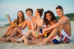Amis avec des boissons se reposant sur une plage Photos libres de droits