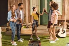 Amis avec des bouteilles de bière passant le temps ensemble Images stock