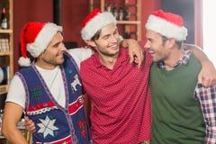 Amis avec des chapeaux de Noël souriant à l'un l'autre Photos stock