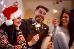 Amis avec des cierges magiques appréciant en partie le jour de Noël Photos libres de droits
