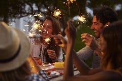 Amis avec des cierges magiques mangeant de la nourriture et appréciant la partie Photographie stock libre de droits