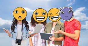 Amis avec des emojis au-dessus des visages utilisant des technologies Photo stock