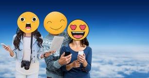 Amis avec des emojis au-dessus des visages utilisant des technologies en ciel Photo stock