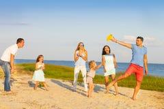 Amis avec des enfants jouant avec le frisbee sur la plage Photos libres de droits