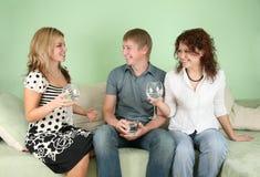 Amis avec des glaces sur le sofa Photo stock